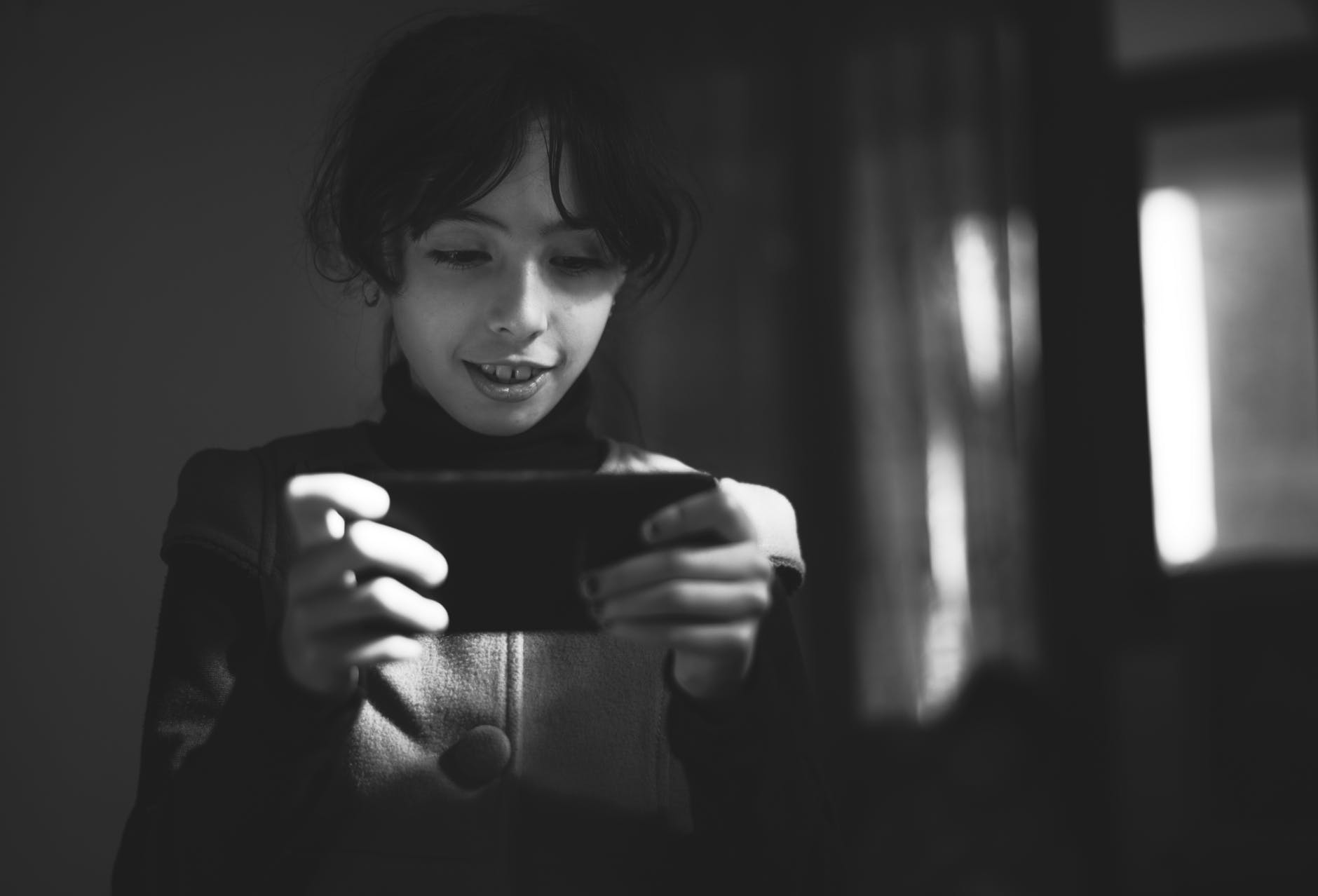 grayscale photography of girl using smartphone - 4 Child Care Trends to Look Out for
